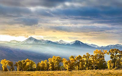 Colorado wall art of sunbeams bursting through clouds in the mountains