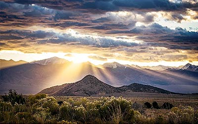 Colorado wall art of dramatic clouds with sunlight on a mountain
